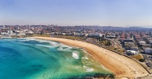 Sydney Bondi beach with bright sand and CBD towers on horizon